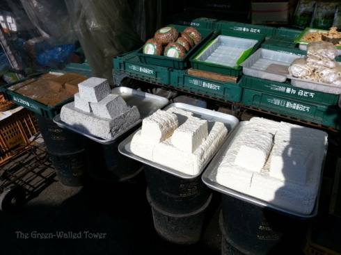Blocks of fresh tofu. The brown blocks to the left are acorn jelly and the round things behind are fermented soy bean paste.